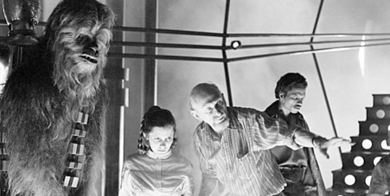 Peter Mayhew (Chewbacca) e Carrie Fisher recebendo instruções de Irvin Kershner. Billy Dee Williams ao fundo.